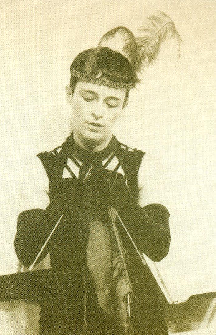 Eine Frau im Ballkleid strickt